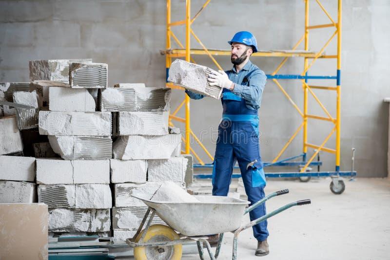 Builder working with blocks indoors. Builder in uniform working with building blocks at the construction site indoors stock image