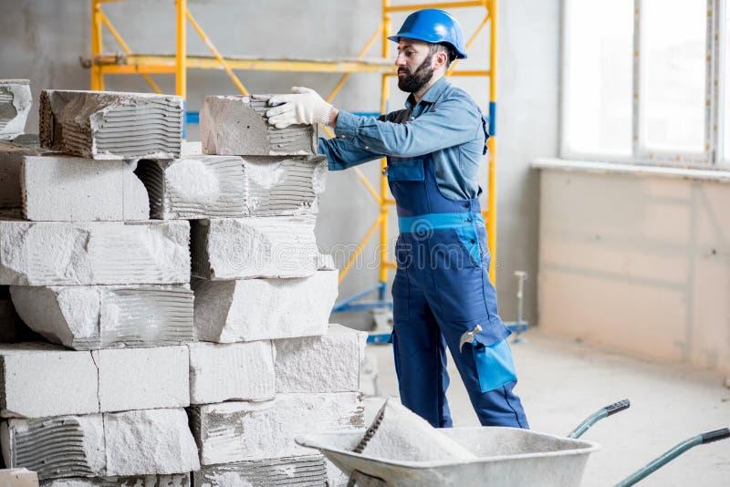 Builder working with blocks indoors. Builder in uniform working with building blocks at the construction site indoors stock photo