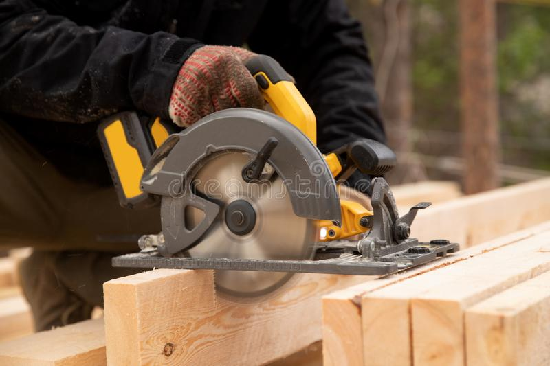 Builder uses portable circular saw tool to cut wood royalty free stock photos