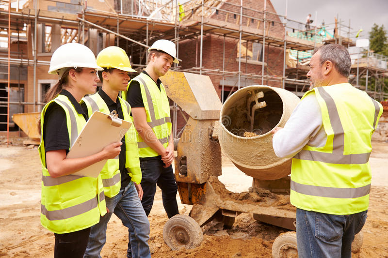 Builder Using Cement Mixer On Building Site With Apprentices stock photography