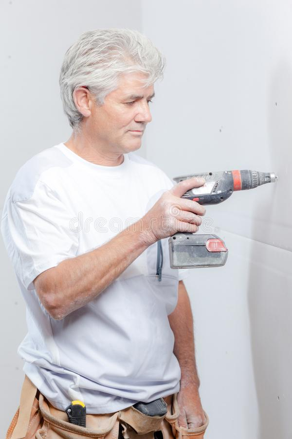 Builder using cordless electric screwdriver. Activity stock photography