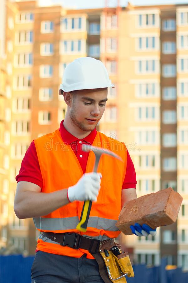 Builder vest and helmet construction site holding brick and hammer in hands royalty free stock image