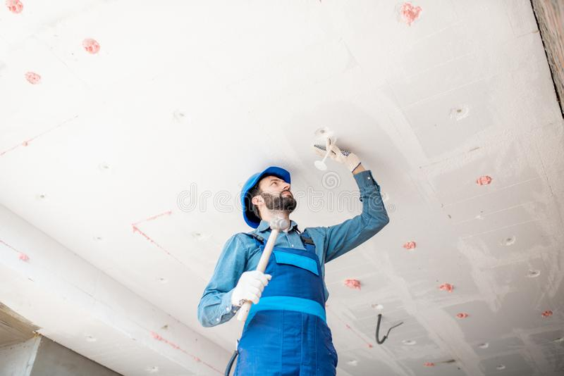 Workman warming the building. Builder warming building ceiling mounting foam panels on the construction site royalty free stock photos