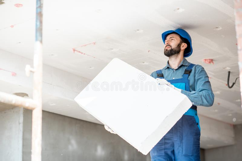 Workman warming the building. Builder warming building ceiling mounting foam panels on the construction site stock photos