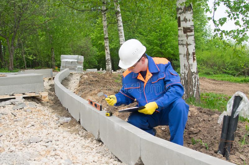 The builder, in a white helmet, blue uniform and yellow gloves, checks the level of the correct installation of the curbstone royalty free stock photos