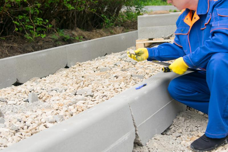 The builder, in a white helmet, blue uniform and yellow gloves, keeps records of road construction and material consumption, on. The left there is a place for royalty free stock photos