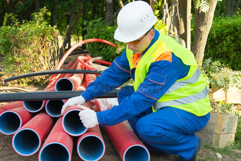 Builder, in a white helmet, pulls out red plastic pipes into a trench, for laying an electric cable through it, close-up stock image