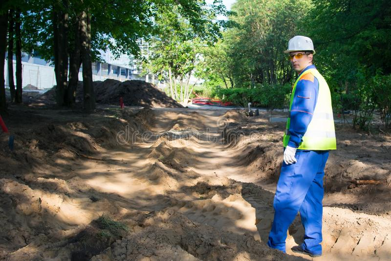 Builder, in a white helmet and a yellow vest, stands on the background of excavated soil, before preparing for the landscape royalty free stock photo