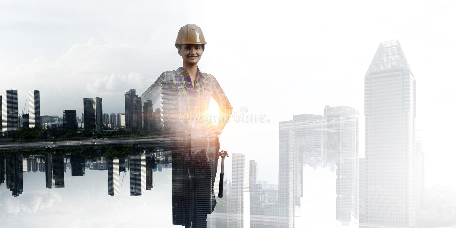 Builder woman against cityscape stock photography