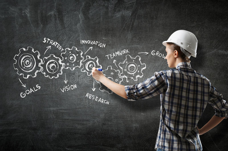 Builder woman draw gear mechanism. Back view of engineer woman in hardhat and sketched concept of teamwork on wall royalty free stock images