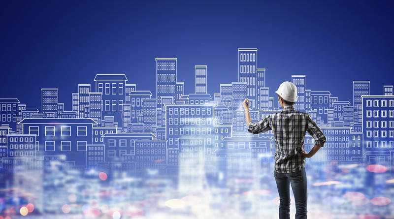 Builder woman sketching city. Engineer woman standing with back and drawing buildings on wall royalty free stock photography