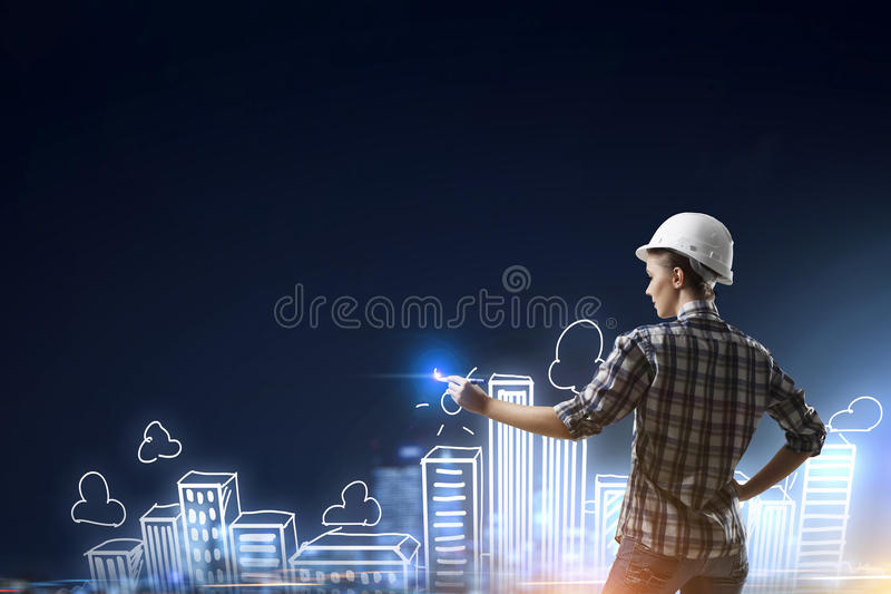 Builder woman sketching city. Engineer woman standing with back and drawing buildings on wall stock image