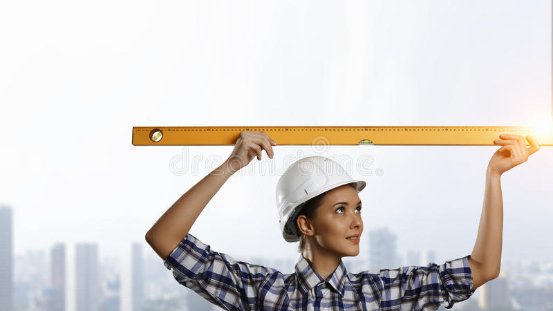 Builder woman taking measures. Mixed media. Attractive engineer woman with yellow measure meter in hands. Mixed media stock photography
