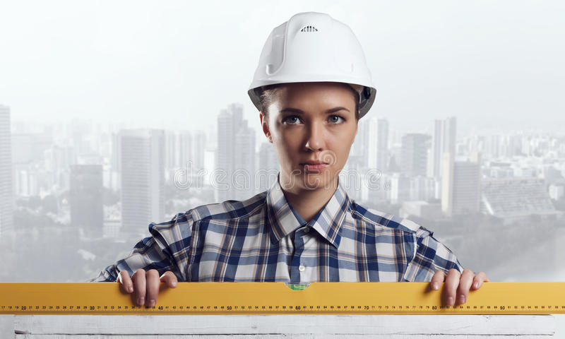 Builder woman taking measures. Mixed media. Attractive engineer woman with yellow measure meter in hands. Mixed media stock images
