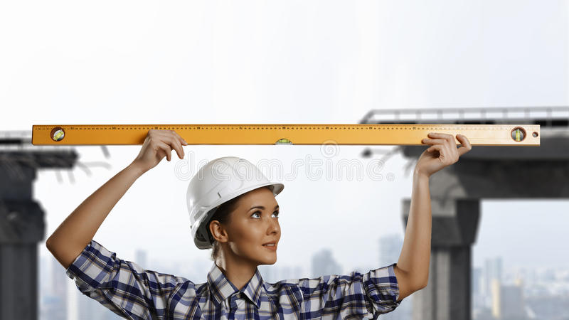 Builder woman taking measures. Mixed media. Attractive engineer woman with yellow measure meter in hands. Mixed media royalty free stock photography
