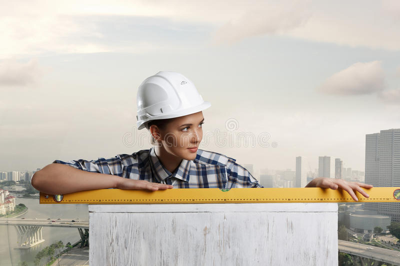 Builder woman taking measures. Mixed media. Attractive engineer woman with yellow measure meter in hands. Mixed media royalty free stock image