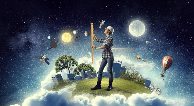 Builder woman taking measures . Mixed media royalty free stock photo