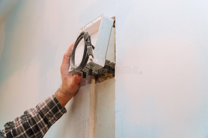 builder at work. cutting wall of electrical work including exposed wires stock image