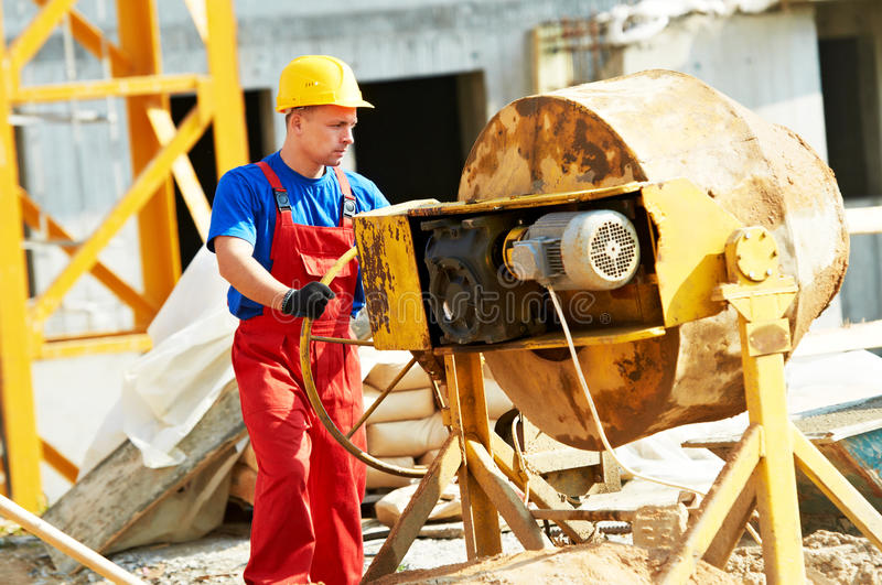 Builder worker at construction with mixer royalty free stock image