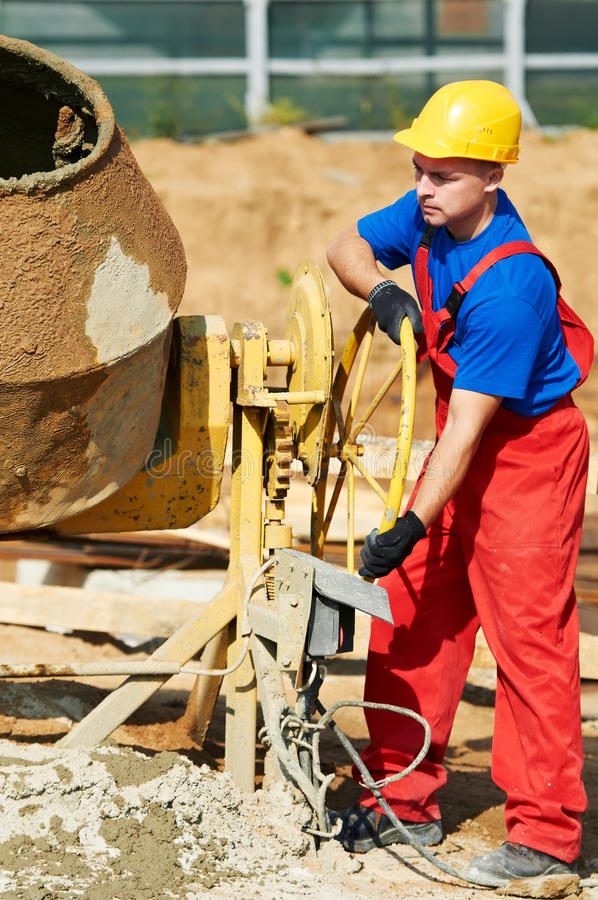 Builder worker at construction site. Builder laborer man working with front of concrete cemant mixer at construction site royalty free stock image