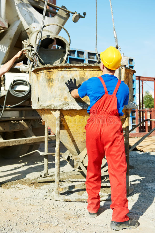 Builder worker at construction site. Builder laborer man working with front of concrete cemant mixer at construction site royalty free stock photos