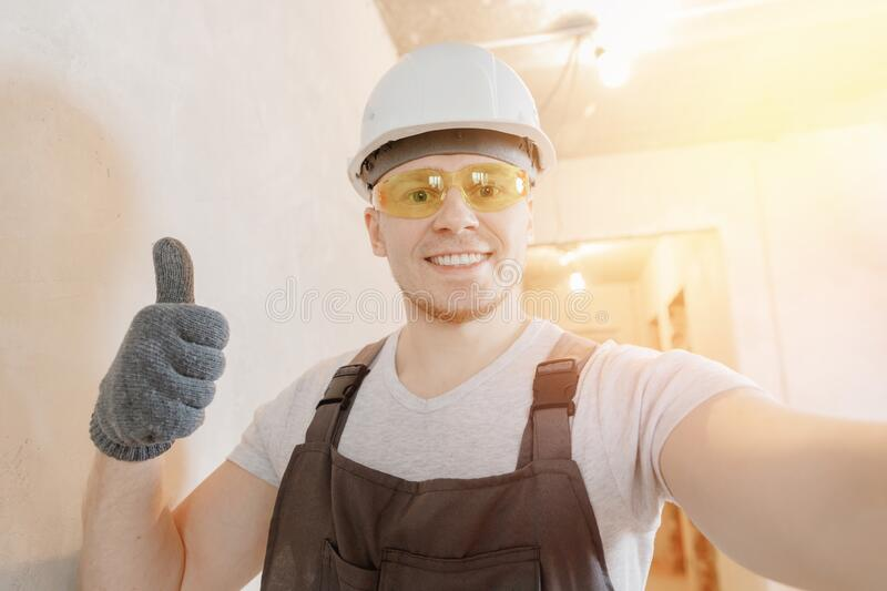 Builder worker man happy makes selfie photo with safety glasses and white helmet royalty free stock photos