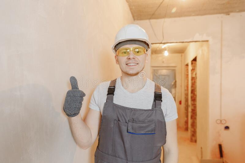 Builder worker man happy with safety glasses and white helmet against background of concrete walls. Concept training in royalty free stock images