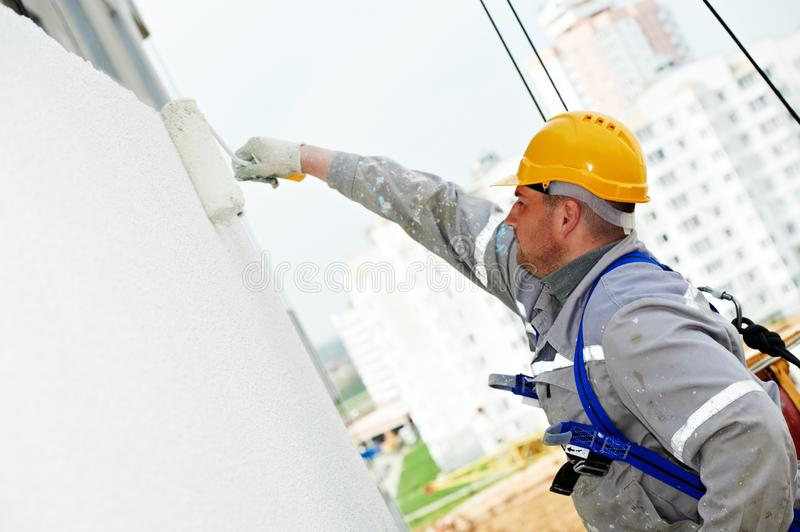 Builder worker painting facade of building with roller stock photo