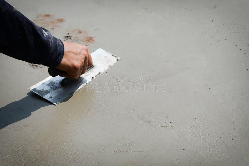 Builder worker plastering concrete cement floor.Hands Plasterer at work stock photo