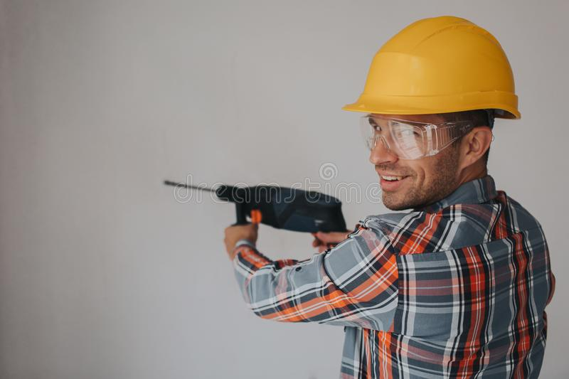 Builder worker with equipment making hole in wall at construction site stock images