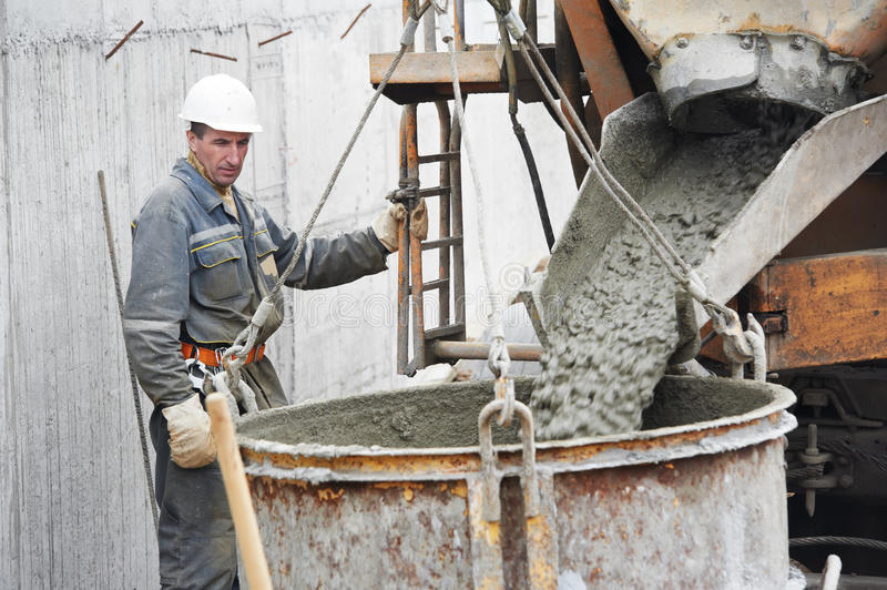 Builder worker pouring concrete into barrel stock photos