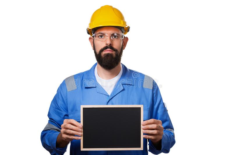 Builder worker in protective construction helmet holding black chalk board with space for informational text, isolated royalty free stock photo