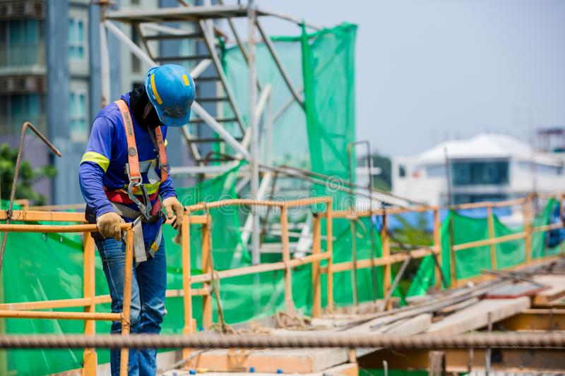 Builder worker in safety protective equipment. Professional industrial climber in helmet and uniform works at height stock images