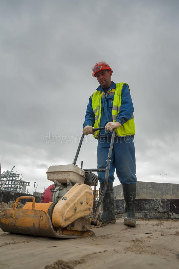 Builder worker with vibration plate royalty free stock photo