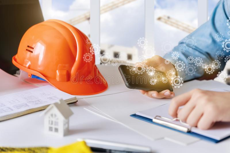 Builder is working on the phone at the Desk. stock image