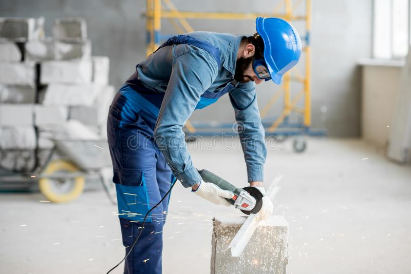 Builder cutting metal indoors. Builder in working uniform cutting metal profile with cutting machine at the construction site indoors royalty free stock photo