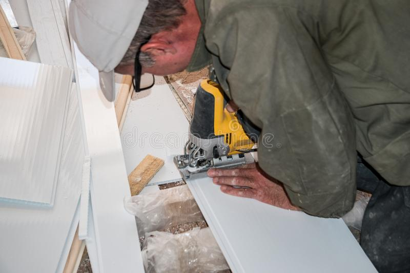 Builder works with white plastic parts stock images