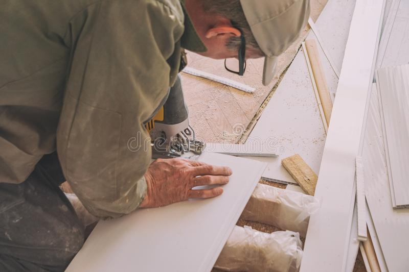 Builder works with white plastic parts royalty free stock photo