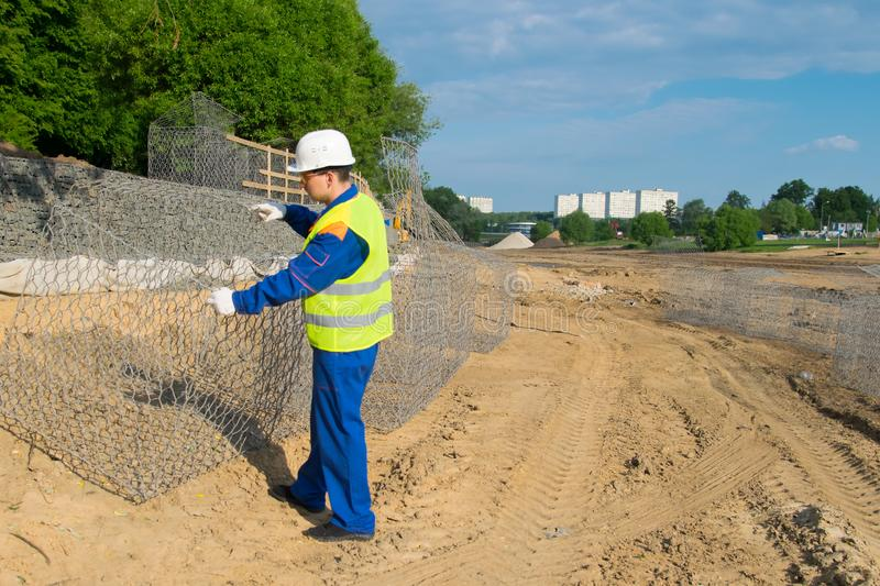 The Builder in a yellow vest and a white helmet, opens a box of mesh to check the design royalty free stock image