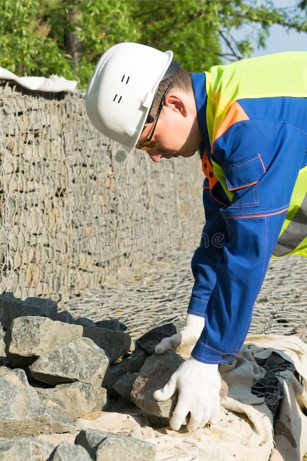 Builder in a yellow vest and white helmet takes a stone. Builder in a yellow vest and  white helmet takes a stone royalty free stock images