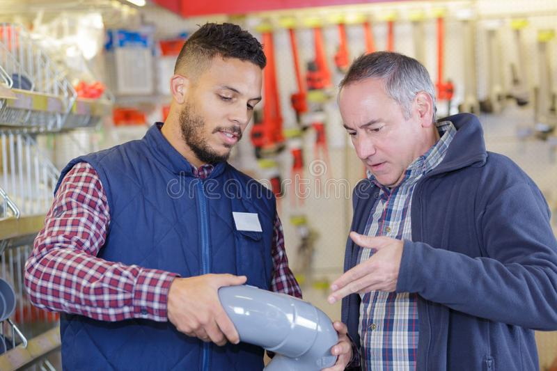 Builders buying plastic pipes at store stock photos