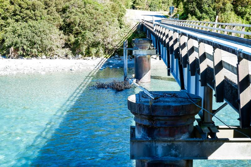 Builders construct a concrete bridge over a small river in New Zealand with cloudy sky royalty free stock images