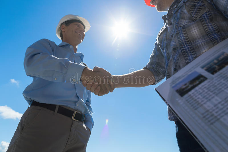 Builders Handshake, Architect And Contractor Agreement During Meeting Discussing Blueprint Buiding Plan On Construction stock photography