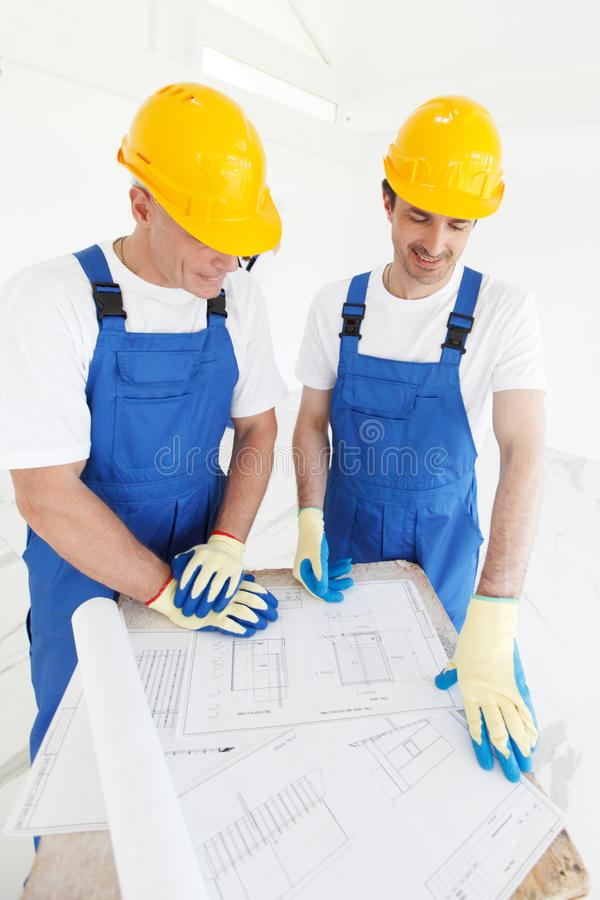 Builders in hardhats with blueprint stock photo