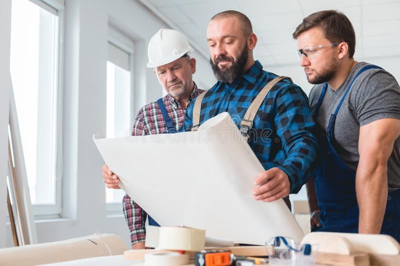 Builders looking at the blueprint royalty free stock photography
