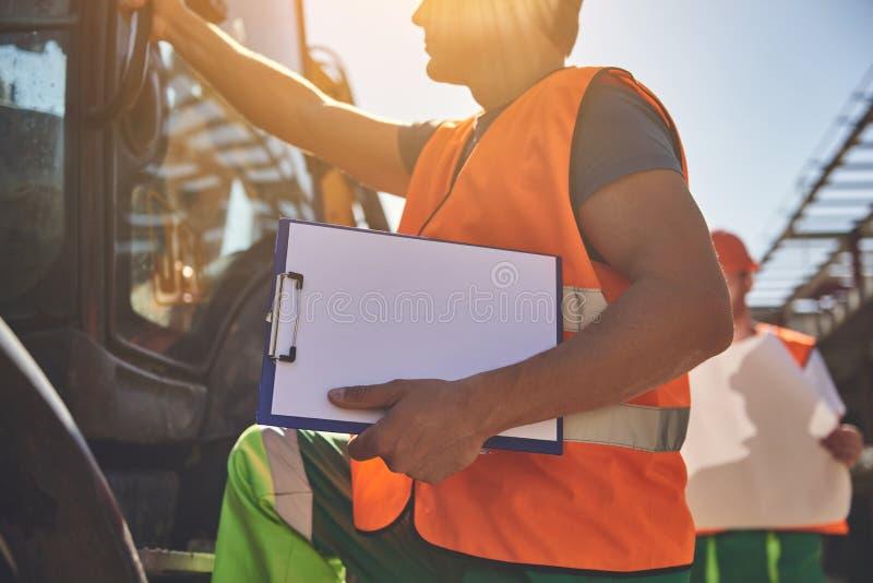 Builders in orange vests are working outdoor stock images