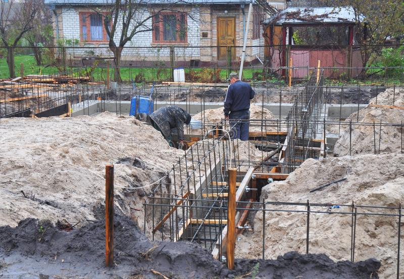 Builders pouring a concrete slab formwork along the foundation. Foundation building. royalty free stock photos