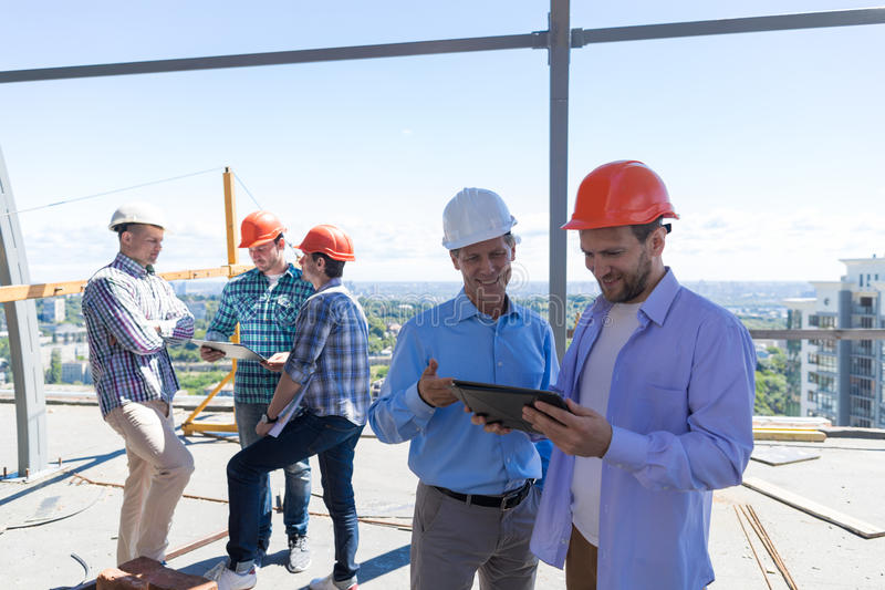 Builders On Site Holding Tablet Computer Discuss Construction Project Over Team Of Apprentices Talking stock image