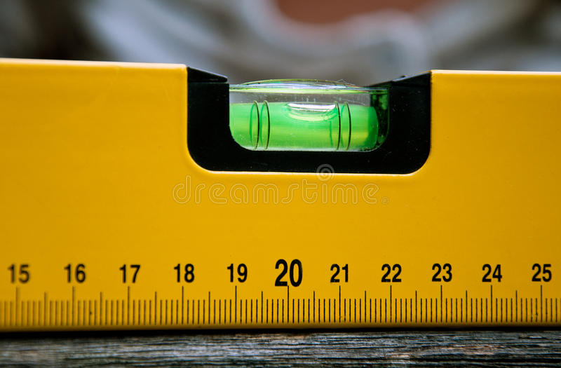 Builders spirit level on a wooden surface stock photography