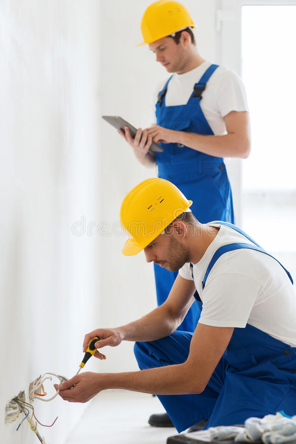 Builders with tablet pc and fixing wiring indoors. Building, renovation, technology, electricity and people concept - two builders with tablet pc computer fixing royalty free stock images